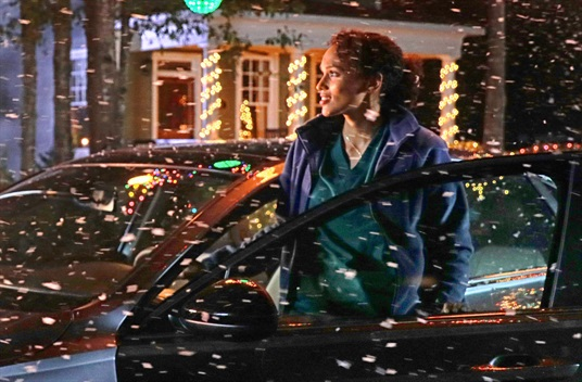 Screenshot from the 2020 Christmas commercial, showing an LMC nurse returning home after work at night, stepping out of her car as snow falls, smiling in surprise at the holiday lights.